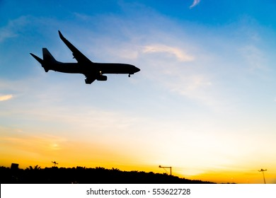 Silhouette airplane while landing gear is down during sunset hours