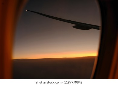 Silhouette airplane wing in sunset moment with blur round window frame.