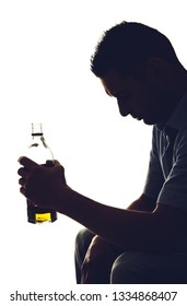 Silhouette of an alcoholic with a bottle whiskey in hand.