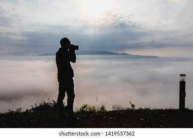 Silhouette of Alone nature Photographer shoots the landscape at the clouds from high up in the hills at Khao Takhian Ngo view point at Khao Kho;Phetchabun; Thailand.