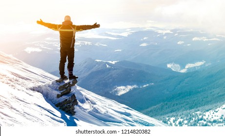 Silhouette of alone tourist standing on snowy mountain top in winner pose with raised hands enjoying view and achievement on bright sunny winter day. Adventure, outdoors activities, healthy lifestyle.