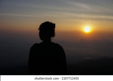 silhouette alone woman seeing sunrise on top of mountain