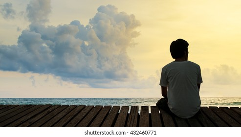 Silhouette alone young man relax siting on beach wooden walk way pier with sunset and cloud sky thinking and concentrate in summer background with copy space for label text banner or advertisement.