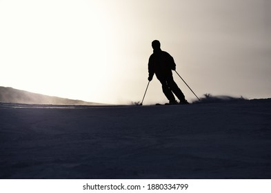 Silhouette alpiner Skifahrer, die in kontrastlichter Helligkeit die Skipiste hinunter fahren