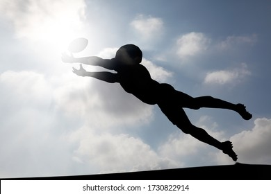 Silhouette of an American football player diving to catch a ball at a touchdown zone against a cloudy blue sky for the concept: Aim for glory.
