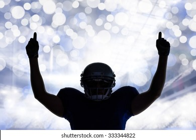 Silhouette American football player with thumbs up against glowing background