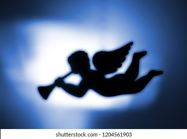 Silhouette of an angel blowing the trumpet, blue-white background