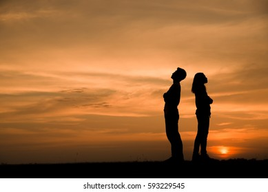 Silhouette of anger of couples love who are quarreling (standing back to back),break up and have something problems with sunset background in Thailand.Anger,unhappy,bad relationship concept.