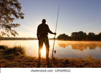 Silhouette of angler standing on the lake shore during misty sunrise