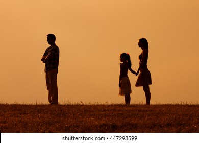 Silhouette of a angry husband turning back while his wife and daughter are looking at him.Angry father turning back on his family