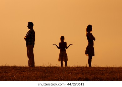 Silhouette of a angry husband and wife on each other with their confused daughter standing in the middle.Parents conflict