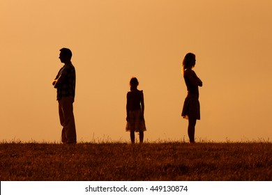 Silhouette of a angry husband and wife  on each other with their daughter standing in the middle.Parents conflict