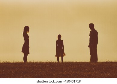 Silhouette of a angry husband and wife  on each other looking at their daughter and waiting for her to choose between them.Heavy choice for a little girl  Image is intentionally with grain and toned.