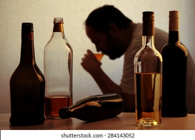 silhouette of anonymous alcoholic person drinking behind bottles of alcohol