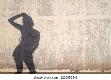 Silhouette of anonymous woman posing over weathered concrete wall on sunny day. She is holding arm on her head.