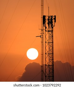 Silhouette Antenna tower and repeater of Communication and telecommunication with the sun on the background at sunset. orange tone