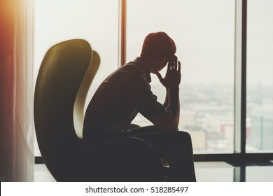 Silhouette of anxious and thoughtful businessman in checkered shirt sitting on yellow armchair and looking into the window of office interior in skyscraper
