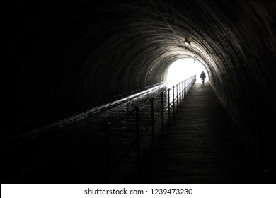 Silhouette Of An Appraching Man In Front Of Bright Light At The End Of A Dark Tunnel