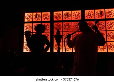 silhouette arab couple in the beautiful windows. Man holding a hookah and bell