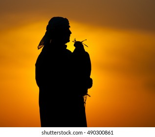 Silhouette of arab man with a falcon on a sunset background.