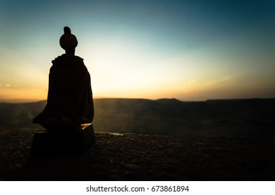 Silhouette of Arab man stands alone in the desert and watching the sunset with clouds of fog