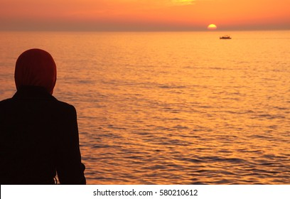Silhouette of arab woman in traditional muslim black hijab or jilbab looking on the beautiful golden sunset in the sea and sailing ship. Back view. Peaceful serene landscape. Middle East.