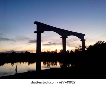 Silhouette of arch with calm river