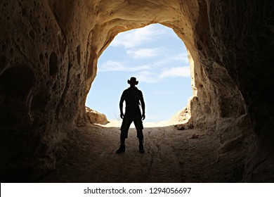 Silhouette of an archaeologist standing in the entrance of an ancient columbarium cave cut into natural rock and used during the Hellenistic and Roman periods. Midras Ruins, Judean lowlands, Israel