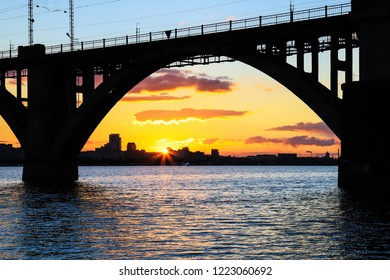 Silhouette of an arched railway bridge on a beautiful sunset on the Dnieper River in the city of Dnipropetrovsk (Dnipro, Dnepr, Dnepropetrovsk) Ukraine.
