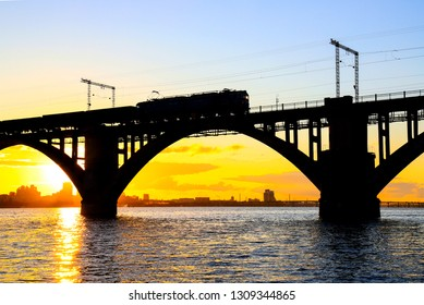 Silhouette of arched railway bridge and a train on the Dnieper river at beautiful sunset. Dnipo city, Dnepropetrovsk,  Ukraine.