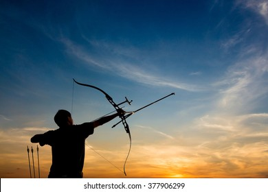 A silhouette of an archer drawing his bow and aiming upwards with colorful and dramatic sky as background