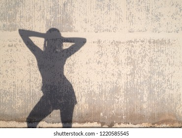 Woman's silhouette with arms behind her head posing relaxed over decayed wall.