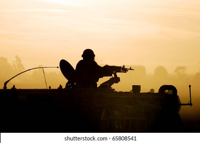 Silhouette of an army soldier preparing his tank and weapons at sunset. Concept photo of war ,military, army, armed forces, incursion,conflict ,firearm ,battle, attack.