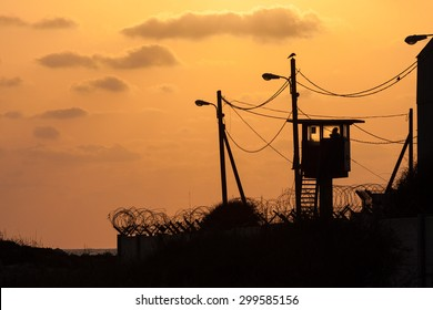Silhouette of army watchtower behind barbed wires at sunset, Israel