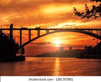 Silhouette of Arrabida Bridge against the sunset sky over the Duoro river, Porto, Portugal