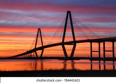 Silhouette of the Arthur Ravenel bridge over the Cooper River in the Charleston Harbor of South Carolina against an orange sky sunset.