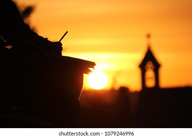 Silhouette of an artist drawing against a sunset background in Greenwich park, London