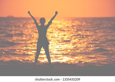 silhouette of asia woman runner hands up to the sky after success  running on the beach in evening, woman enjoying the sunset, healthy freedom concept