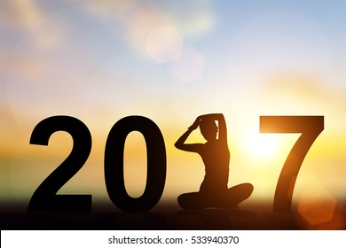 Silhouette Asia woman yoga in 2017 text on the beach at sunset. Happy new year 2017