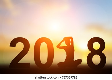 Silhouette Asia woman yoga in 2018 text on the beach at sunset. Happy new year