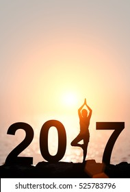 Silhouette Asia woman yoga in Happy new year 2017 text on the beach at sunset.