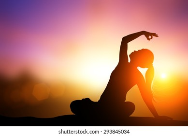 Silhouette Asia woman yoga on the beach at sunset.