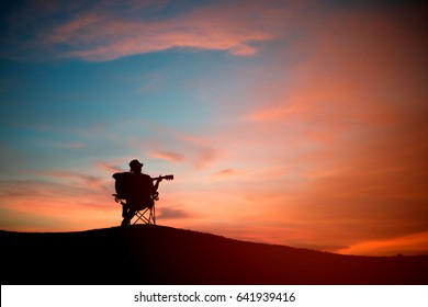 Silhouette of asia young man with playing acoustic guitar, sunset background