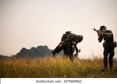 Silhouette of Asian army soldier carries a wounded soldier evacuate at across the deep forest.