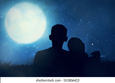 Silhouette of asian couple looking the moon in the sky at night