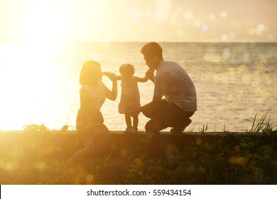 Silhouette of Asian family outdoor activity, enjoying holiday together on seaside in beautiful sunset during vacations.