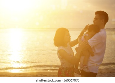 Silhouette of Asian family outdoor portrait, enjoying holiday together on seaside in beautiful sunset during vacations.
