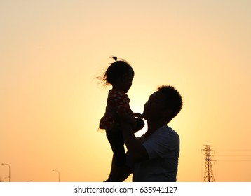 silhouette of a asian father hold up his daughter under sunset. background of father's day