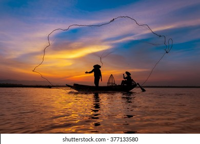 Silhouette asian fisherman on wooden boat casting a net for catching freshwater fish in nature river in the early morning before sunrise