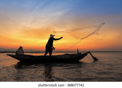 Silhouette of asian fisherman on wooden boat in action casting a net for catching freshwater fish in nature river in the early morning before sunrise